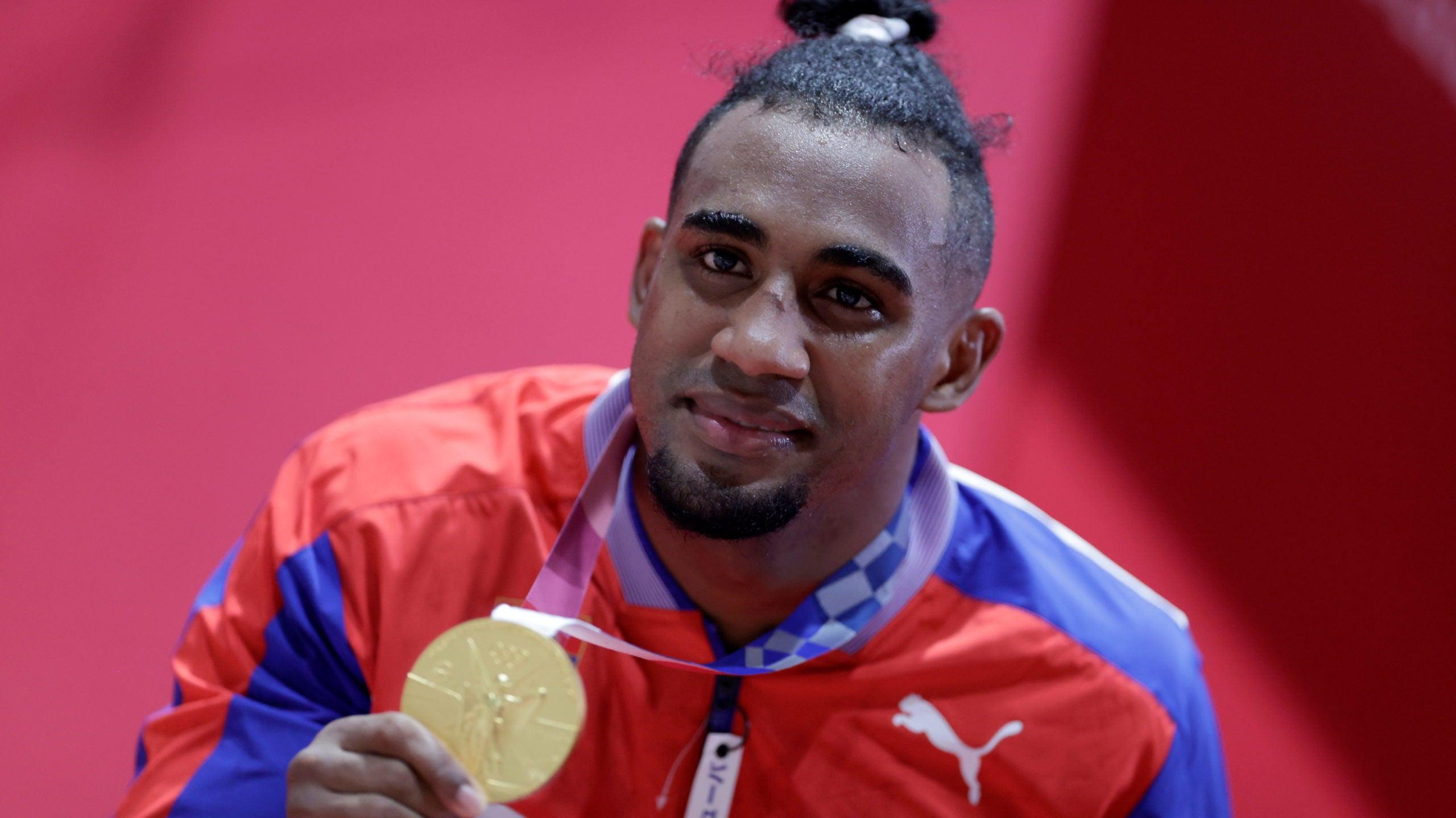 Gold medallist Arlen Lopez Cardona of Cuba poses for photos.